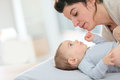 Mother and her baby boy cuddling on a changing table Royalty Free Stock Photo