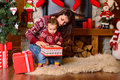 Mother and her baby daughter opening a christmas gift happy family little playing in Stock Photo
