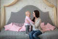 Mother with her baby daughter playing on the couch in a real roo room casual lifestyle happy family sofa Royalty Free Stock Photo