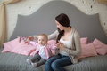 Mother with her baby daughter playing on the couch in a real roo room casual lifestyle happy family sofa Stock Photos