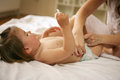 Mother with her baby at home. Mother changing diaper her little