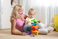Mother and her child playing with colorful logical toy Royalty Free Stock Photo