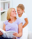 Mother with her cute smiling daughter reading Royalty Free Stock Photography
