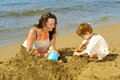Mother and her daughter playing with toys and sand at beach Royalty Free Stock Photo
