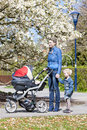Mother and her daughter with a pram on spring walk Stock Photo