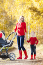 Mother and her daughter with a pram on walk in autumnal alley Royalty Free Stock Images
