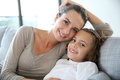 Mother with her daughter smiling on sofa cute little girl mom sitting in Stock Photography
