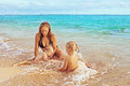 Mother and her daughter and son on the sea beach beautiful smiling young with two little cute children boy girl playing joyfully Royalty Free Stock Photo