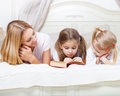 Mother and her daughters reading bed time story book in Royalty Free Stock Images