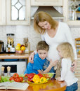 Mother and her kids in kitchen Stock Image