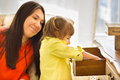 Mother with her little daughter girl is looking for something in a chest of drawers and smiling mom Royalty Free Stock Photography