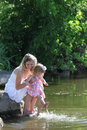 Mother and her little daughter squirting water at the lake Royalty Free Stock Photography