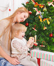 Mother with her little daughter under the christmas tree happy Royalty Free Stock Photography