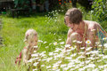 Mother and her little daughter young cute picking flowers on a lush summer meadow full with ox eye daisies Stock Photography