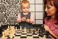 Mother and her little doughter near chess board Stock Images