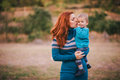 Mother and her little son in a knitwear have a walk in a forest wearing blue sweaters having an autumn Royalty Free Stock Photo