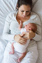 Mother with her newborn baby son lying in bed Royalty Free Stock Photo