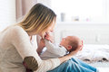 Mother with her newborn baby son sitting on bed Royalty Free Stock Photo