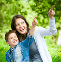 Mother and her son with book sitting on green grass pointing hand gesture in park concept of happy family relations carefree Stock Photos
