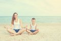 Mother and her son doing yoga on coast of sea on beach. Royalty Free Stock Photo