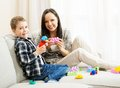 Mother with her son on a sofa happy young playing building kit Stock Image