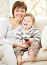Mother and her son are watching tv while sitting on a couch Royalty Free Stock Photography