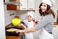 Mother and her son in white chef hats preparing an omelet in the kitchen. Royalty Free Stock Photo