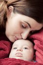 Mother with her young baby cuddling and kissing him on forehead parenthood love Stock Image