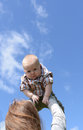 Mother holding baby boy against blue sky flying up with a smile Stock Photography