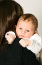 Mother is holding baby boy newborn on grey background Stock Photo
