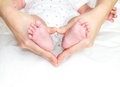 Mother holding baby s feet both together Stock Photo