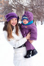 Mother holding a baby, snow, winter park Royalty Free Stock Image