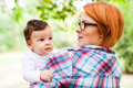 Mother holding cute baby girl outdoors in a garden Royalty Free Stock Image