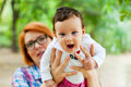 Mother holding cute happy baby girl outdoors in a park Stock Photos