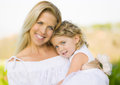 Mother holding daughter flower girl a smiling happy blue eyed with a white dress and long blond hair closely and lovingly holds Stock Photos