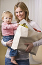 Mother Holding Daughter and Groceries Royalty Free Stock Photo