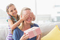 Mother holding gift with daughter covering her eyes Royalty Free Stock Photo