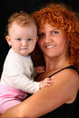 Mother holding her baby daughter on black backgrou Stock Images