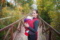 Mother holding her baby daughter, outside on wooden bridge Royalty Free Stock Photo