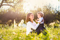 Mother holding her little son sitting on the grass in sunny nature Royalty Free Stock Photo