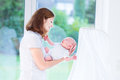 Mother holding her newborn baby next to crib Royalty Free Stock Photo