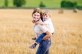 Mother holding kid boy on arms on wheat field in summer Royalty Free Stock Photo