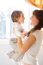 Mother holding little son against window Royalty Free Stock Images