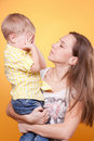 Mother holding little son hiding eyes Royalty Free Stock Image