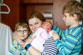 Mother holding newborn baby girl on arm with two kids boys Royalty Free Stock Photo