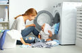 Mother a housewife with a baby  fold clothes into the washing ma Royalty Free Stock Photo