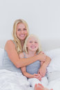 Mother hugging her daughter in bed Stock Photo