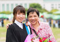 Mother is hugging her daughter for her master degree graduation with university gown Stock Photos
