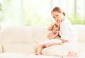 Mother hugging and protects her baby daughter on the sofa Royalty Free Stock Photography