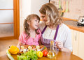 Mother and kid cook and communicate in kitchen Royalty Free Stock Photo